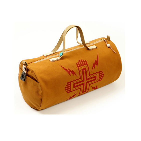 Ochre canvas duffel bag with Navajo red hand printed cross and bolts. Buffalo stone cross detail, military spec cotton webbing straps and bridle leather detail. Military spec Knight Mills name tape.